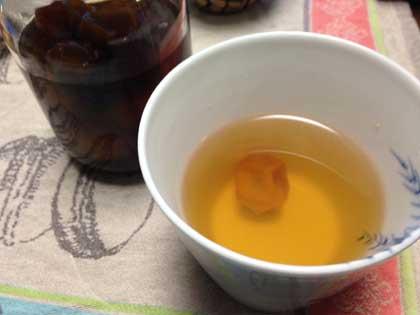 焼酎のお湯割りに金柑の甘露煮を入れて