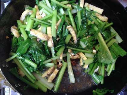 イワシの切り込みをニンニクと一緒に炒め、小松菜と油揚げを投入